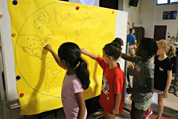 Students leave their fingerprint on a map of the world.