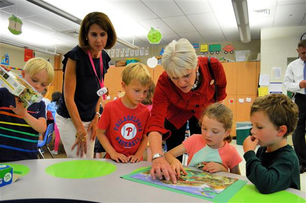 Representative Carolyn Comitta helps kindergarten students complete their puzzle.